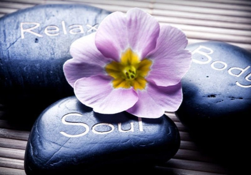 three massage stones - relax, body, soul - and a flower like a concept for wellness, reiki, body care and yoga symbols
